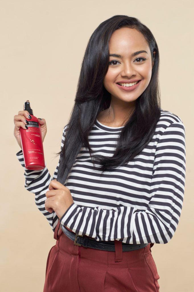 Wanita asia dengan rambut hitam menata gaya rambut pin up hair menyemprotkan spray rambut