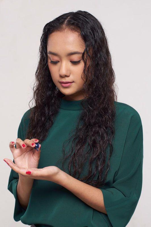 Wanita asia dengan rambut keriting panjang warna hitam menggunakan vitamin rambut – cara meluruskan rambut keriting.