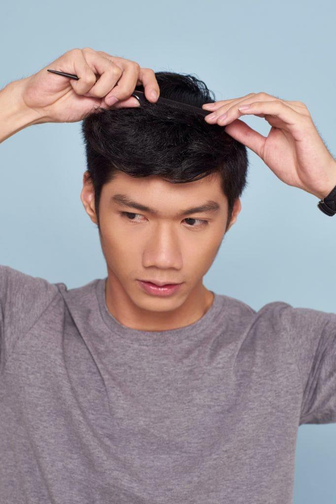 Pria asia dengan warna rambut hitam menata rambut gaya quiff dengan sisir.