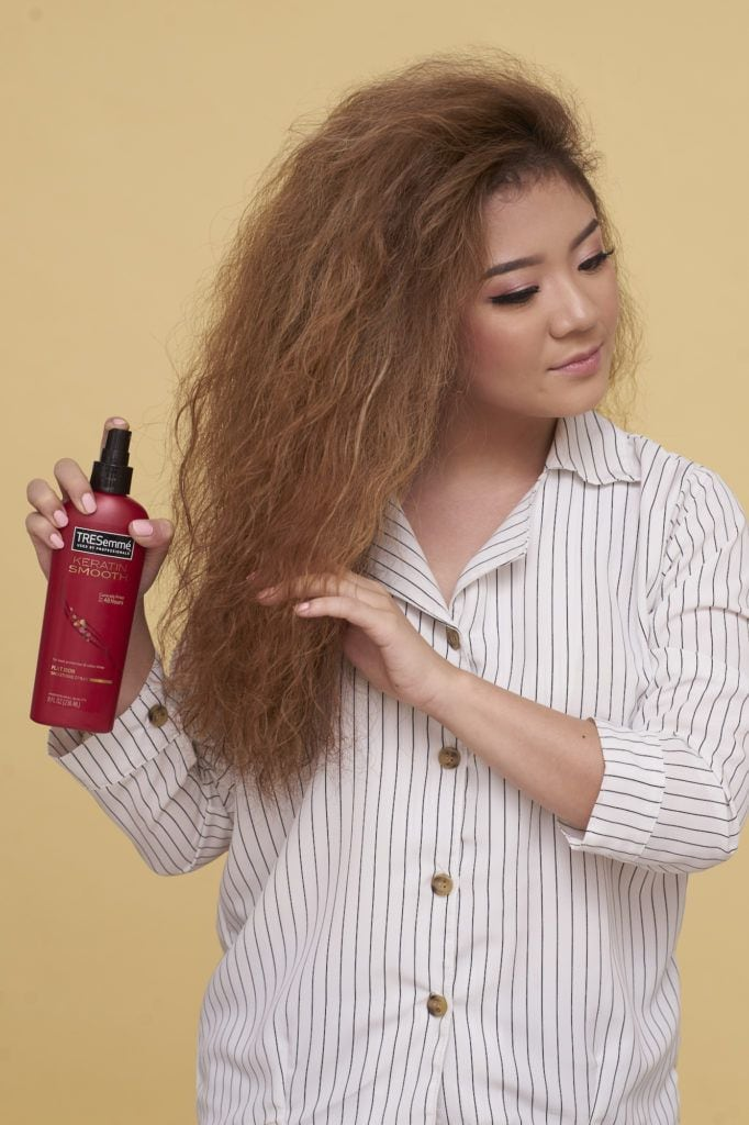 Wanita asia dengan rambut cokelat menggunakan heat protection spray