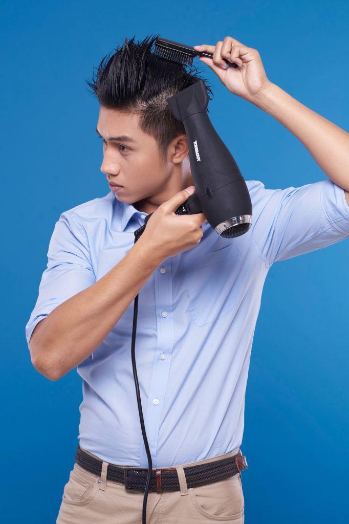 Pria asia dengan warna rambut hitam sedang menyisir rambut sambil mengeringkan – tutorial menata gaya rambut pompadour