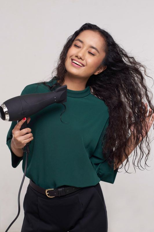 Wanita asia dengan rambut keriting panjang warna hitam menggunakan hairdryer – cara meluruskan rambut keriting.