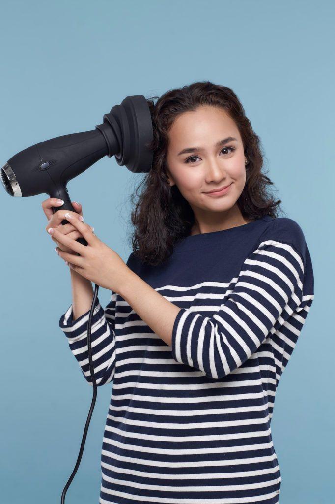 Wanita asia dengan rambut keriting pendek warna hitam mengeringkan akar rambut.