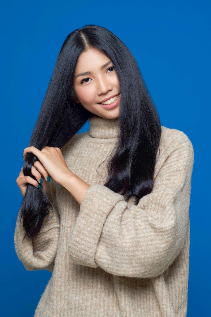 Wanita asia dengan rambut hitam panjang menyisir rambut dengan jari – cara mengatasi rambut kusut.