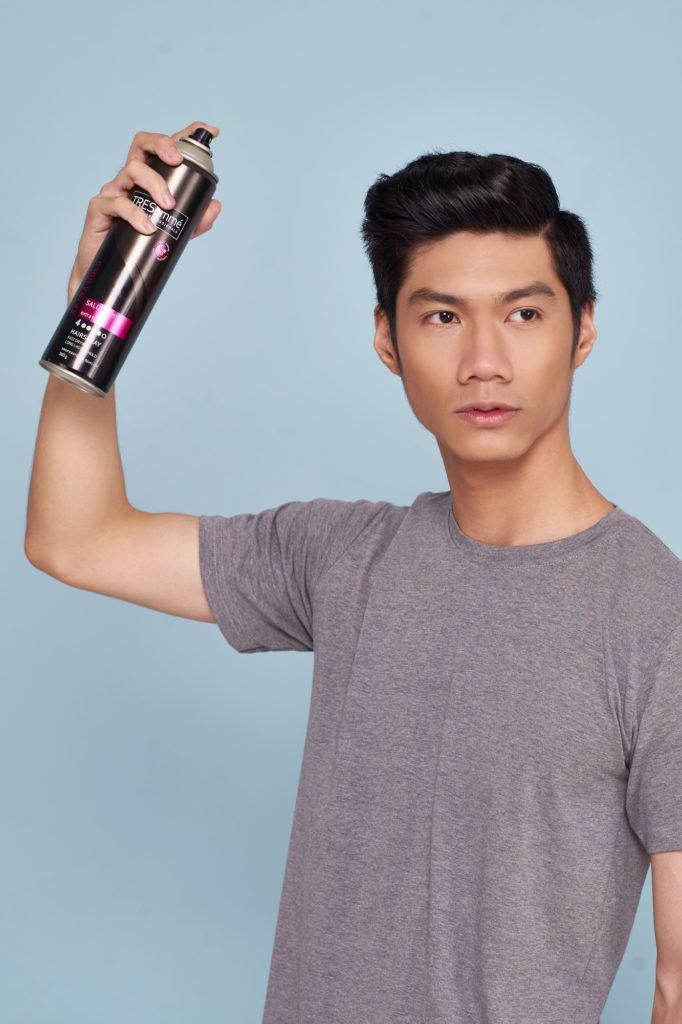 Pria asia dengan rambut hitam menyisir rambut ke belakang untuk menata gaya rambut quiff.