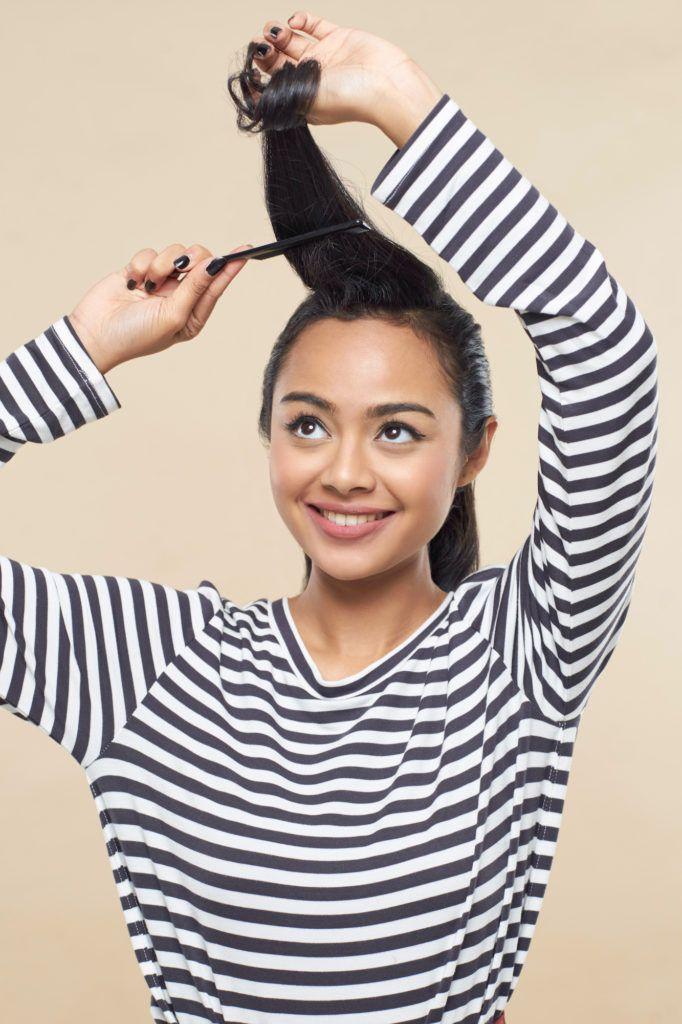 Wanita asia dengan rambut hitam menyasak rambut membentuk gaya pin up hair.
