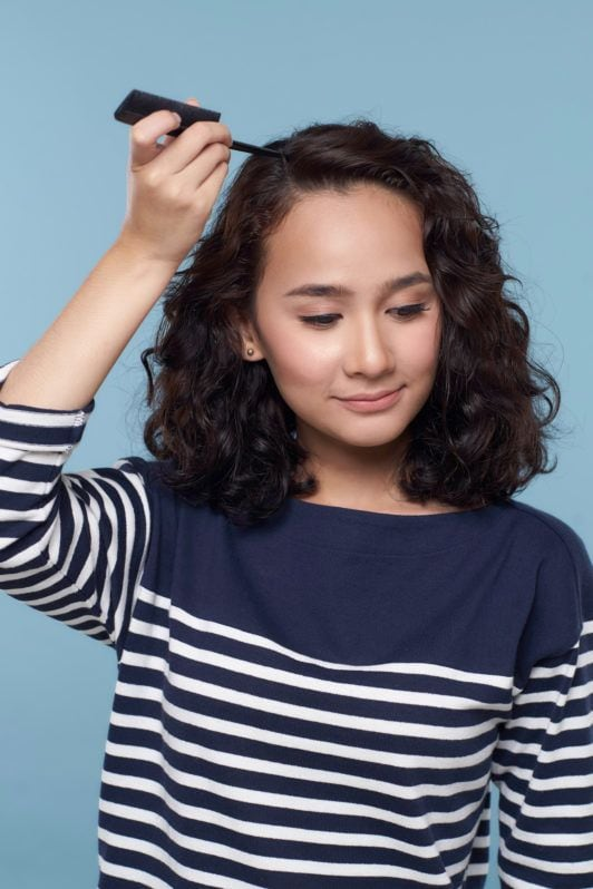 Wanita asia dengan rambut keriting pendek warna hitam membelah rambut.