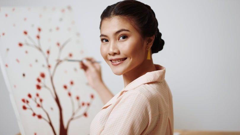 Wanita asia dengan warna rambut hitam model rambut sanggul sedang melukis - double dutch braid bun