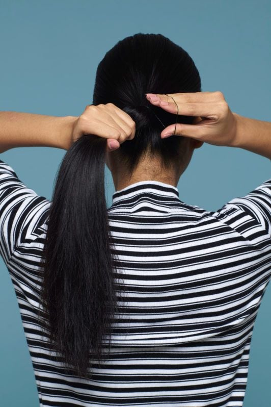 Wanita asia sedang membentuk ponytail pada rambut hitam panjang