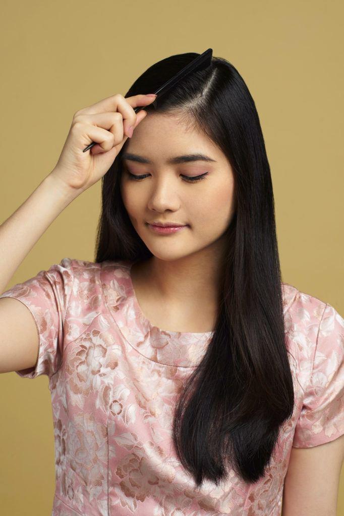 Wanita asia dengan model rambut hitam panjang membelah samping rambut - side part sleek low bun