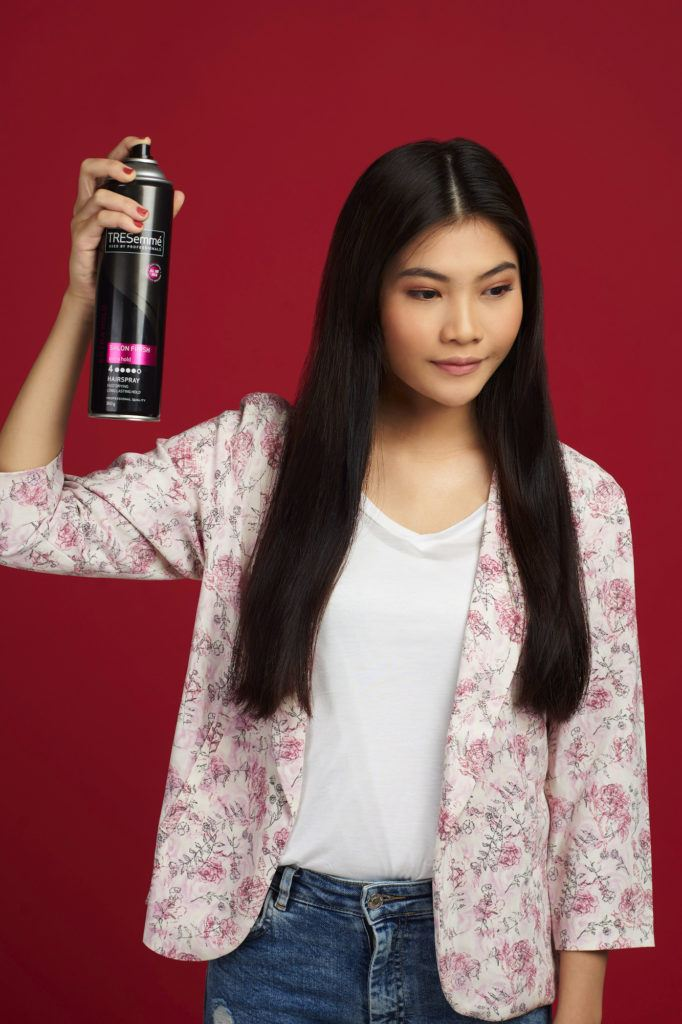Wanita asia dengan rambut hitam panjang menyemprotkan hairspray - double french twist ponytail