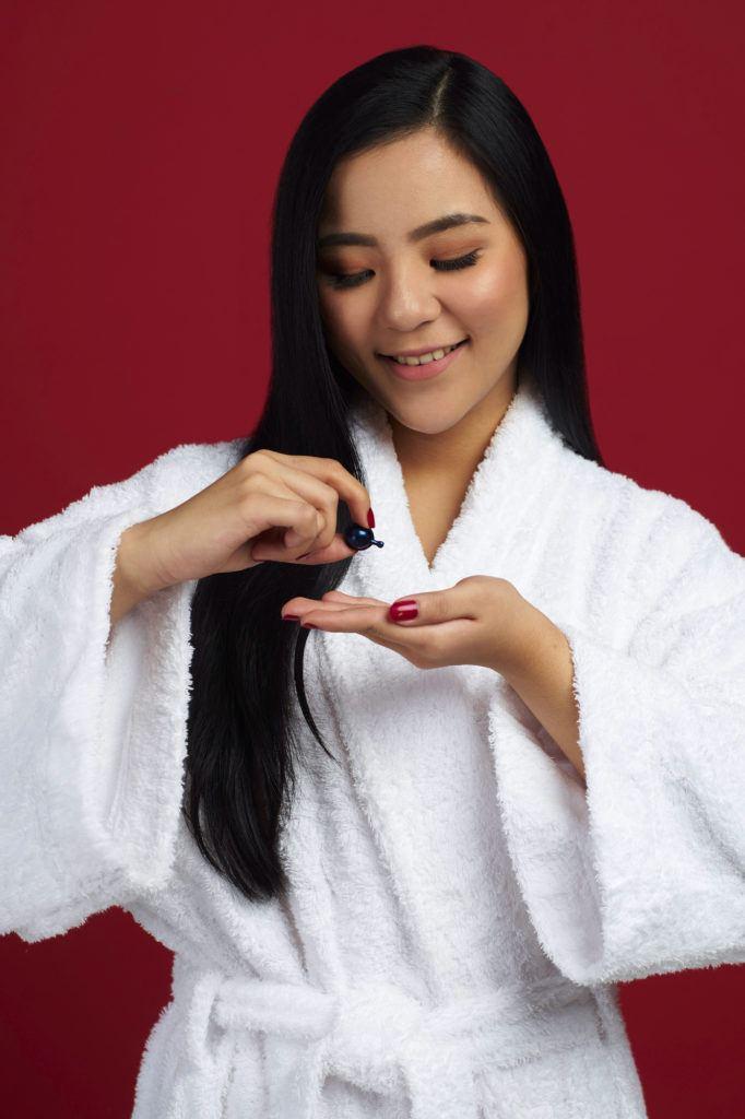 Wanita asia dengan rambut hitam panjang menggunakan vitamin rambut - sanggul pengantin modern untuk wajah bulat