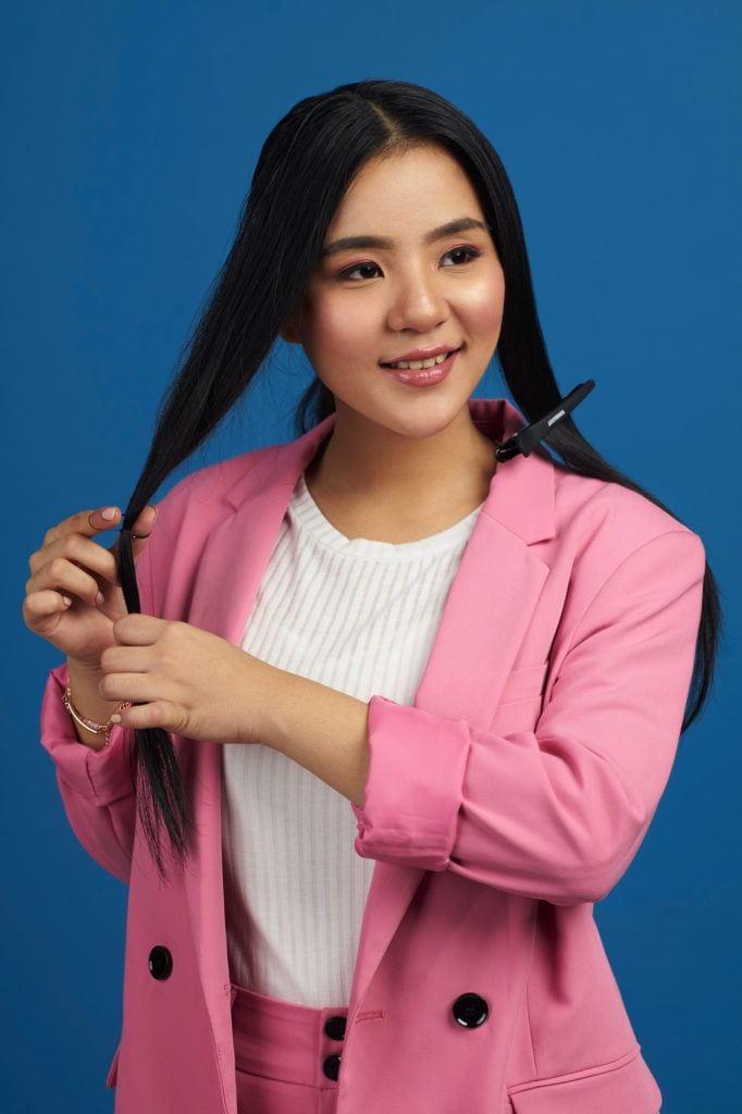 Wanita asia dengan rambut hitam panjang menata rambut tucked in ponytail
