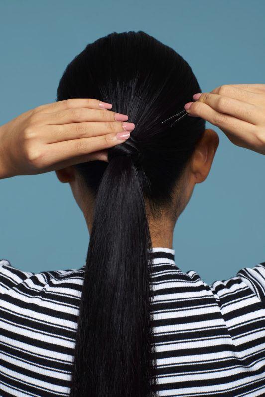 Wanita asia dengan rambut hitam lurus panjang menata ponytail.