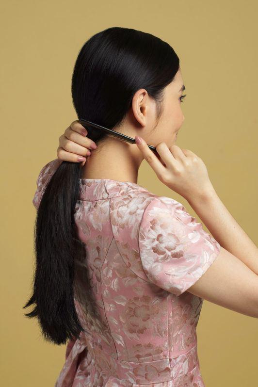 Wanita asia dengan model rambut hitam panjang menyisir rambut - side part sleek low bun
