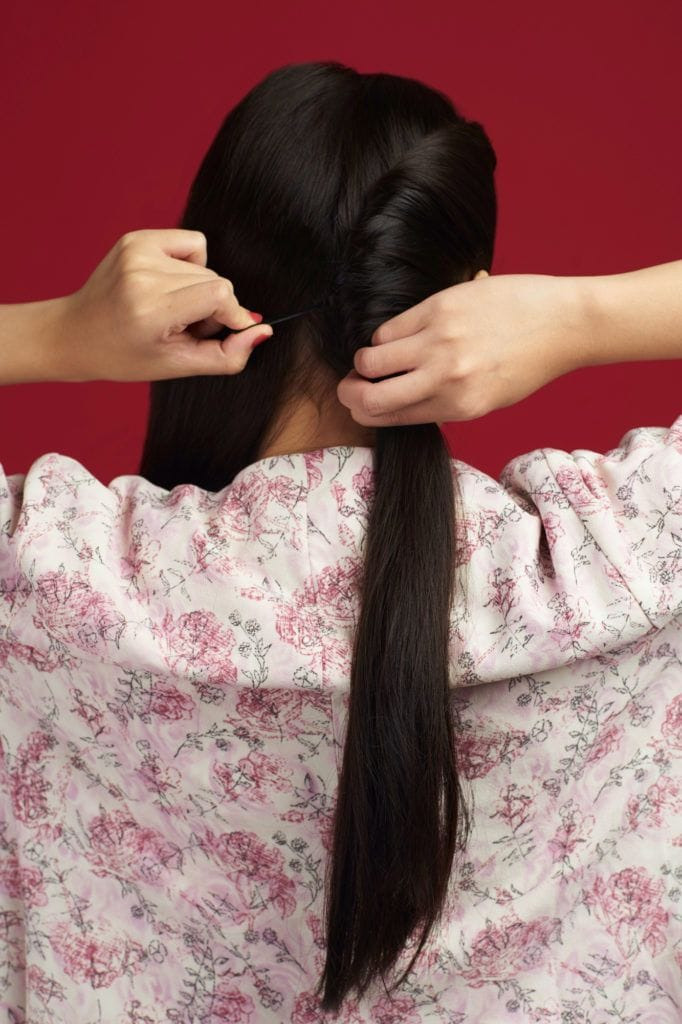 Wanita asia dengan rambut panjang hitam menata twist pada rambut - double french twist ponytail