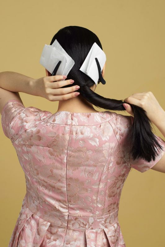 Wanita asia dengan model rambut hitam panjang menata ponytail - side part sleek low bun