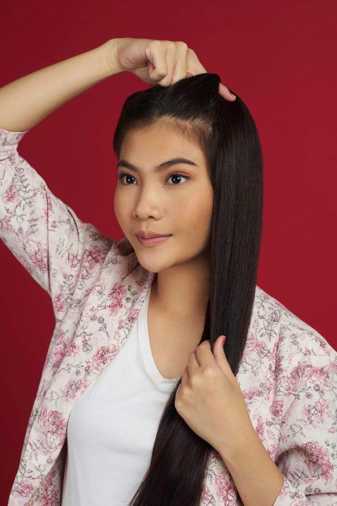 Wanita asia dengan rambut panjang hitam membuat french twist - double french twist ponytail