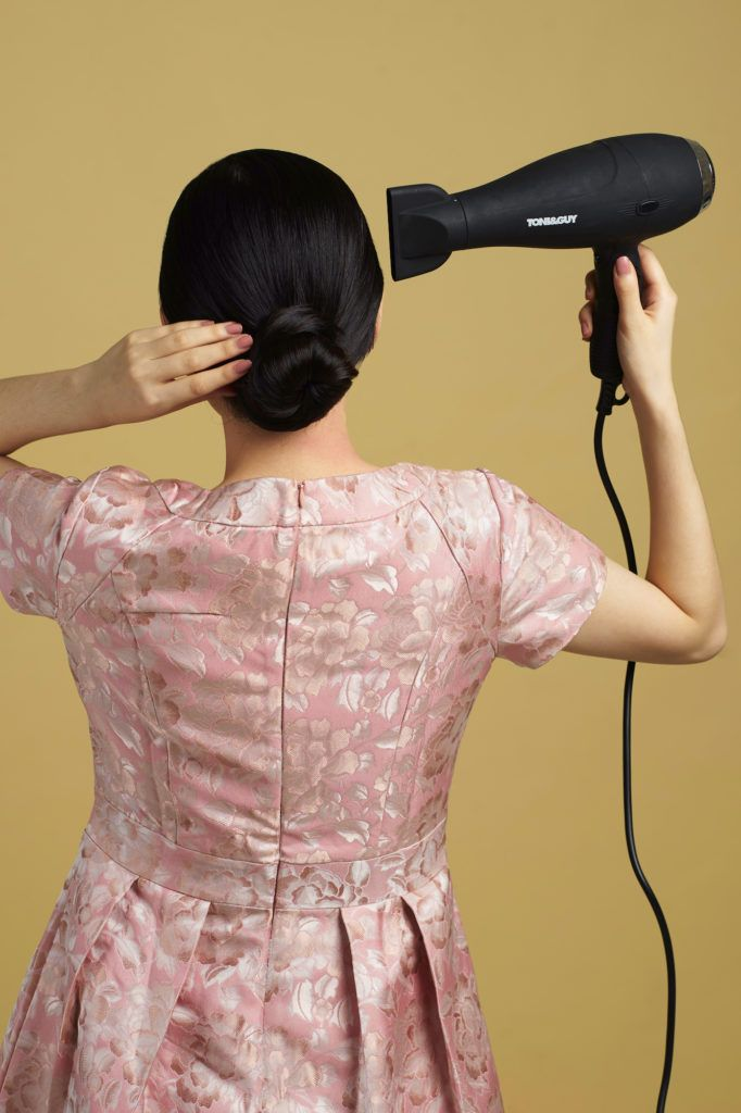 Wanita asia dengan model rambut hitam panjang menyemprotkan hairspray - side part sleek low bun