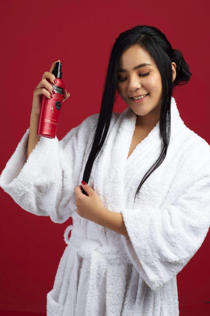 Wanita asia dengan rambut hitam panjang menyemprotkan heat protection spray - sanggul pengantin modern untuk wajah bulat