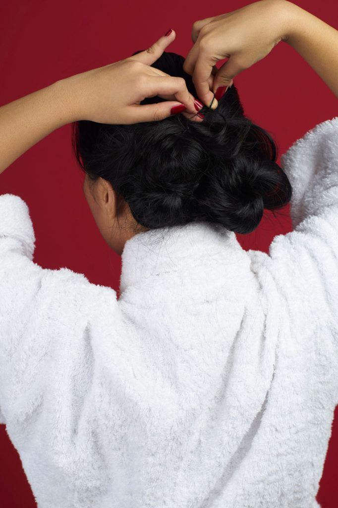 Wanita asia dengan rambut hitam panjang membuat cepol rambut -sanggul pengantin modern untuk wajah bulat