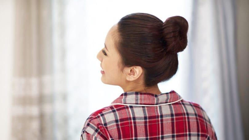 Wanita asia dengan warna rambut merah dan gaya rambu cepol pada rambut panjang