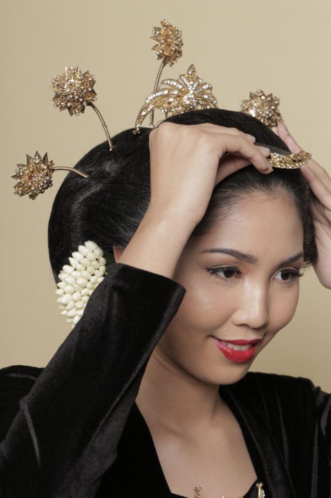 Wanita Asia memasang hiasan pada rambutnya