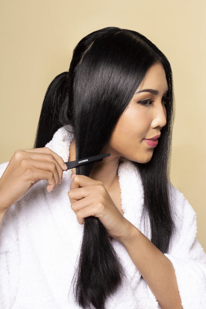 Wanita asia dengan rambut hitam panjang sedang menjepit rambut - sanggul pengantin jawa