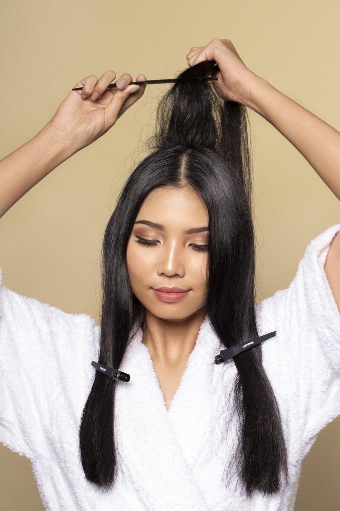 Wanita asia dengan rambut hitam panjang sedang menyasak rambut - sanggul pengantin jawa