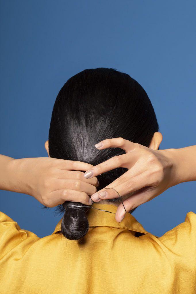 Wanita asia dengan rambut panjang membentuk cepol pada ponytail
