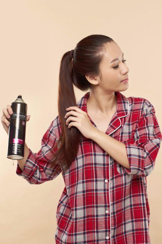 Wanita asia dengan rambut warna merah menyemprotkan hairspray pada rambutnya - cepol rambut panjang