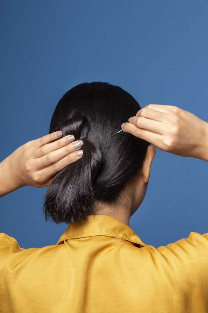 Wanita asia dengan rambut hitam menata gaya looped and knotted ditata dengan jepit