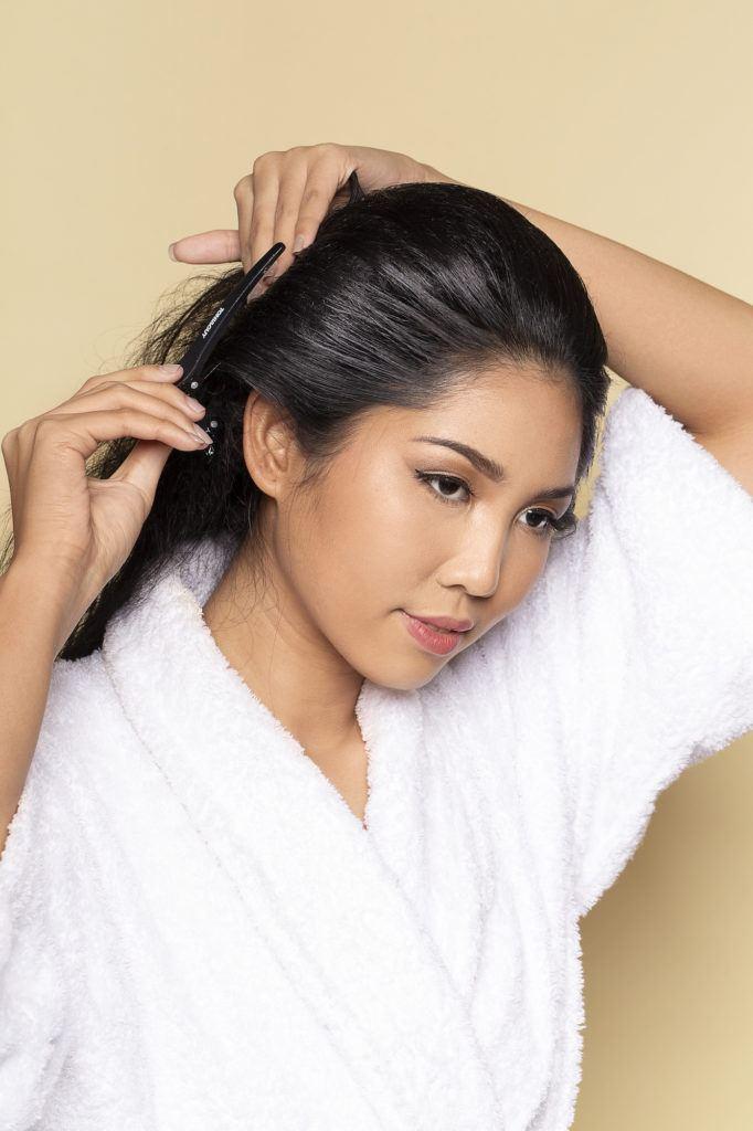 Wanita asia dengan rambut hitam panjang sedang menjepit sasak rambut - sanggul pengantin jawa