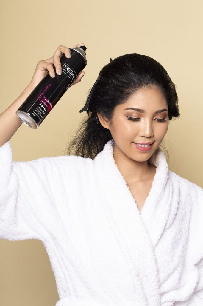 Wanita asia menyemprotkan rambut dengan hairspray