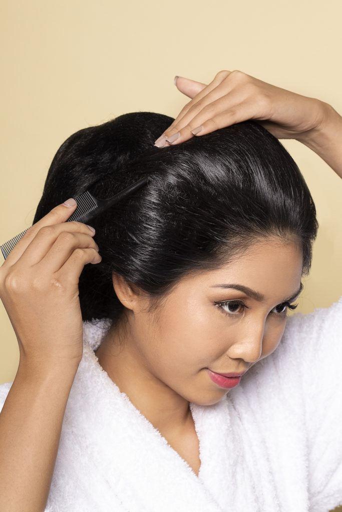 Wanita asia menata kembali sasak rambut
