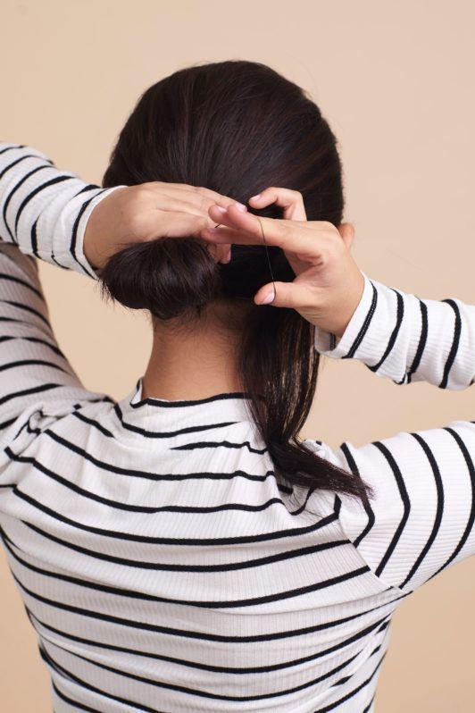 Wanita asia dengan rambut pendek menata cepol - cepol rambut pendek