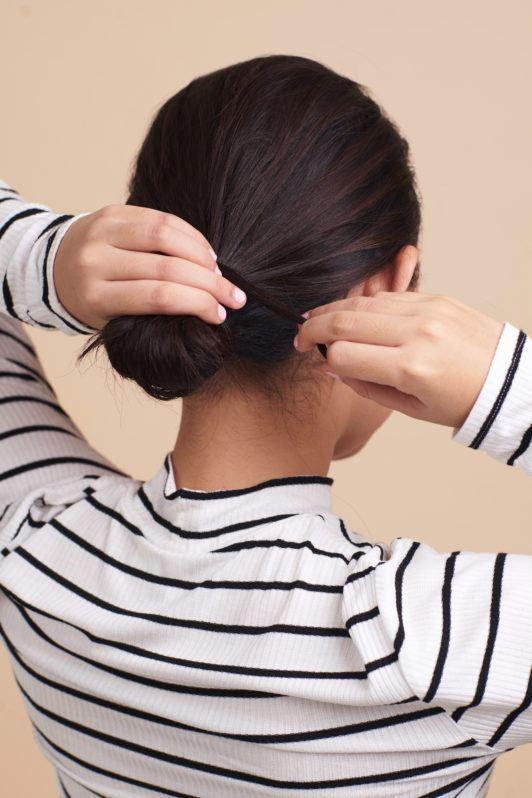 Wanita asia dengan rambut pendek melingkarkan rambut pada cepol - cepol rambut pendek