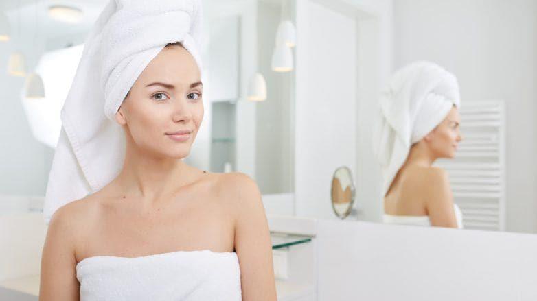 Perempuan tersenyum ke kamera usai keramas dalam balutan handuk tebal di kepalanya