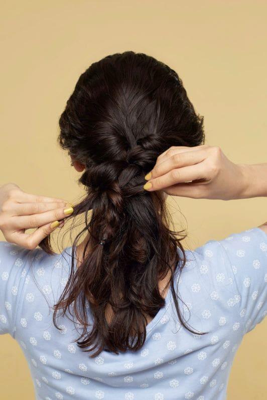 Wanita asia dengan model rambut mermaid braid membuat kepang di belakang kepala
