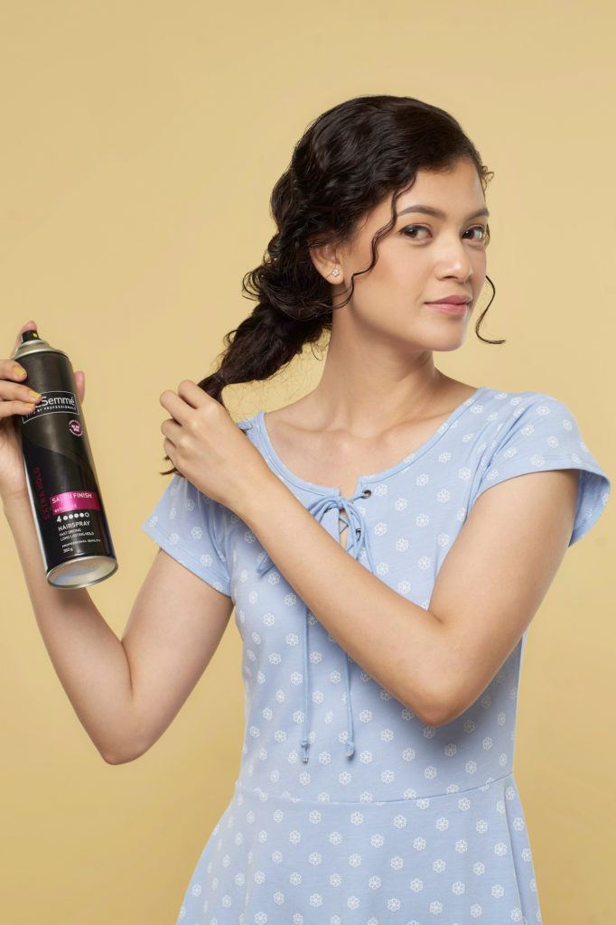 Wanita asia dnegan rambut keriting cokelat gaya mermaid braid menyemprotkan hairspray