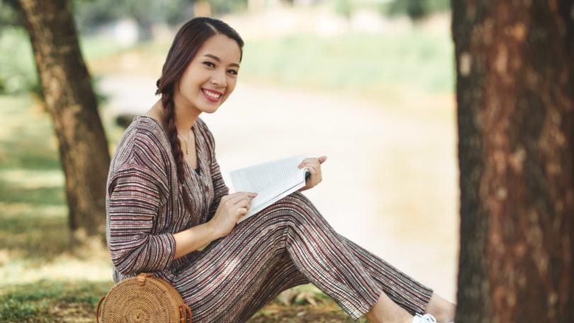 Wanita asia dengan model rambut french braid samping membaca buku di pinggir sungai