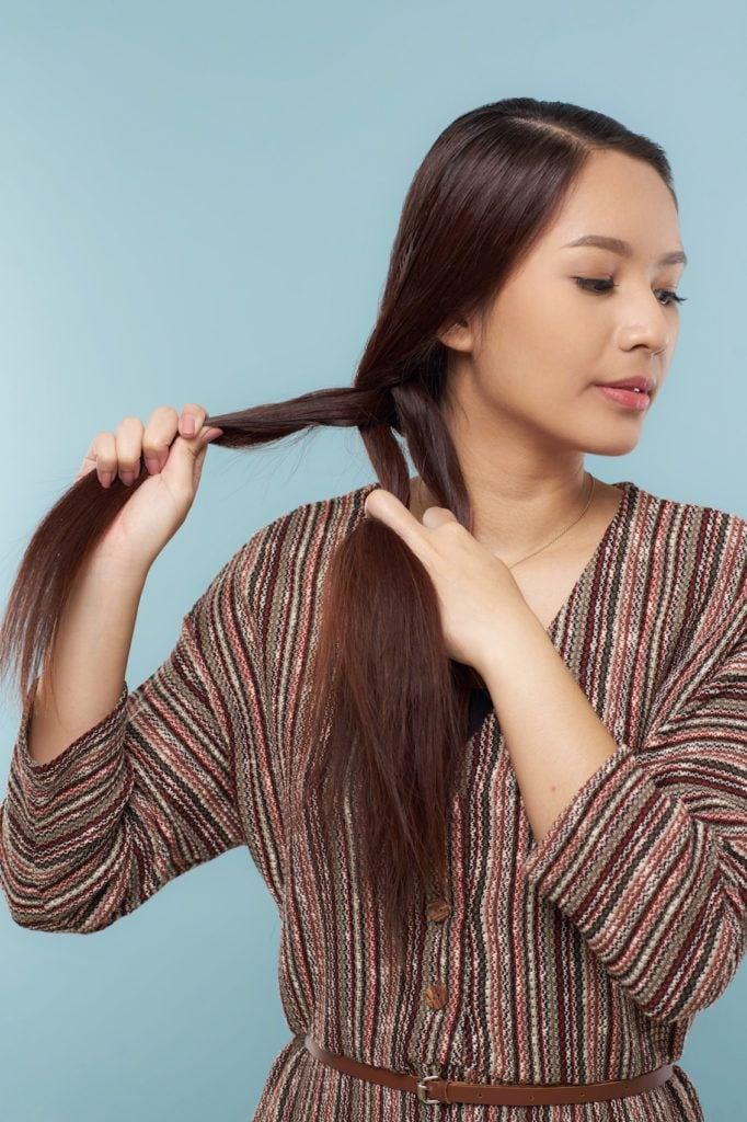Wanita asia dengan model kepang meneruskan mengepang rambut