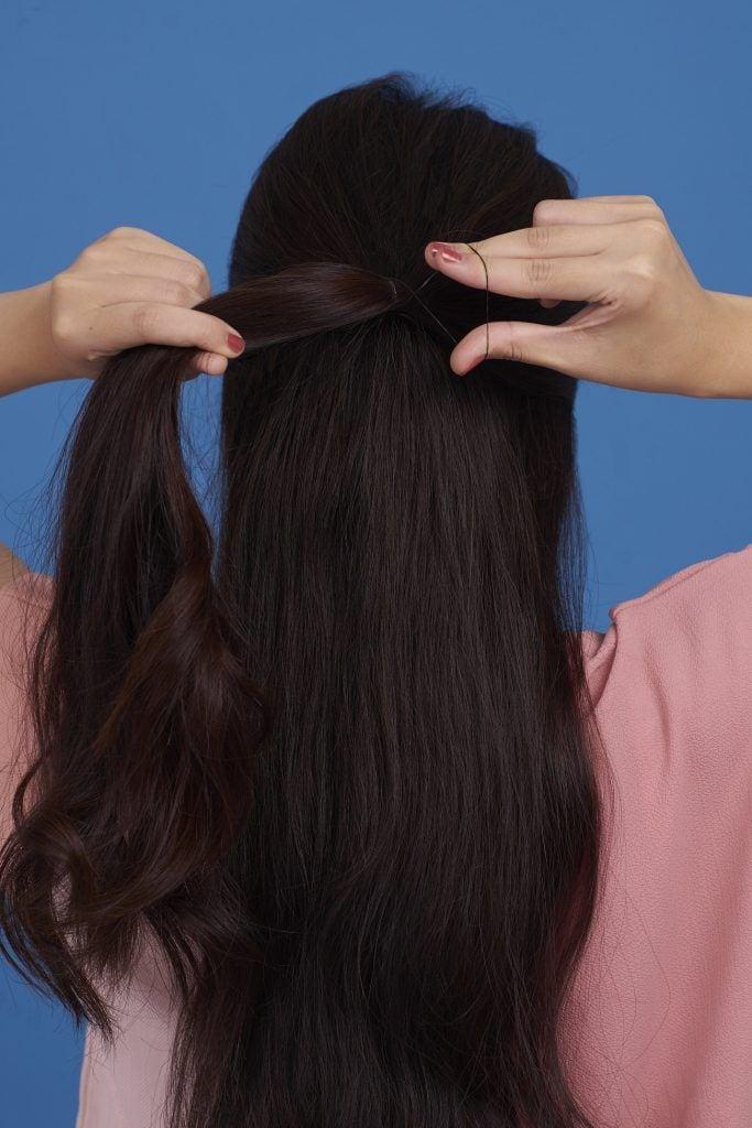 Wanita Asia sedang mengikat rambut untuk membuat fishtail braid