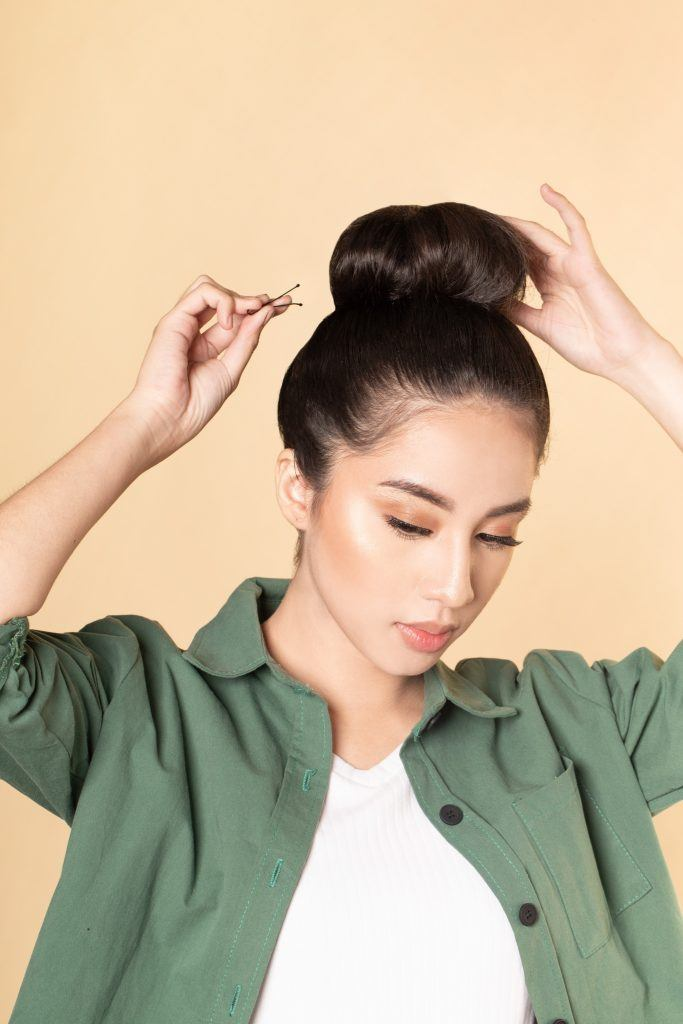 Wanita asia dengan rambut hitam memasang jepit para top knot