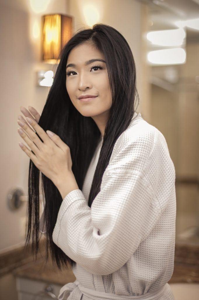 Wanita Asia sedang mengoleskan vitamin rambut