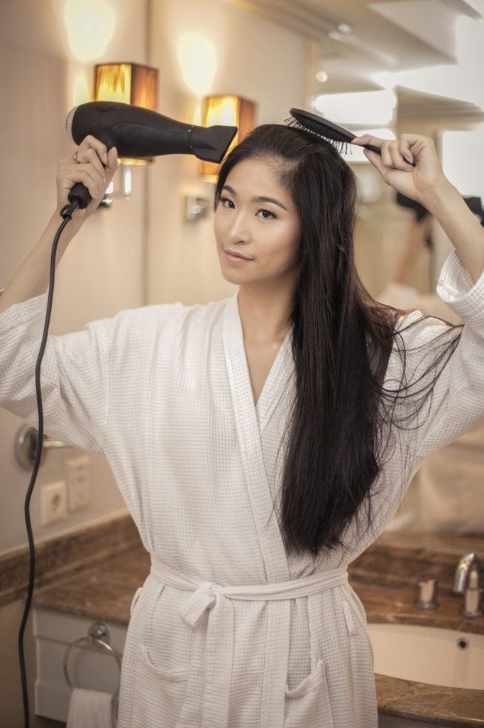 Wanita Asia sedang mengeringkan rambut dengan hairdryer setelah keramas
