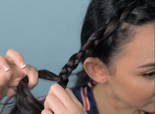 Wanita Asia sedang mengepang rambut