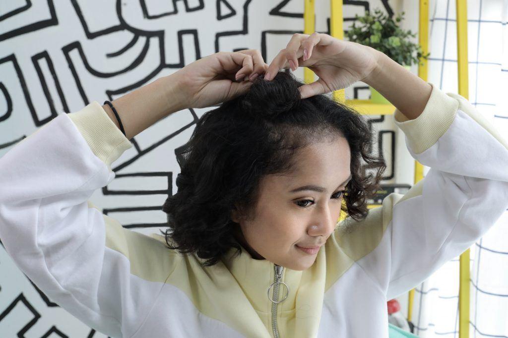 Wanita asia dengan model rambut half space bun untuk rambut keriting