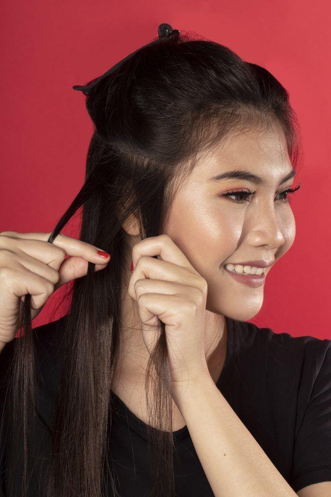 Wanita asia dengan rambut hitam membagi rambut untuk mengepang