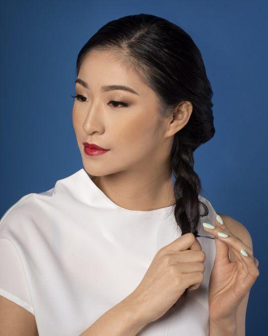 wanita asia dengan baju putih menata rambutnya dengan gaya sanggul kepang lilit